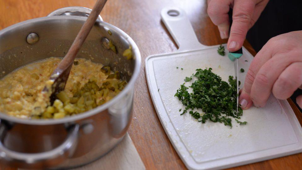 Do zchladlé směsi přidáme na kostičky nakrájené kyselé okurky, nasekanou petrželku a lžíci hořčice