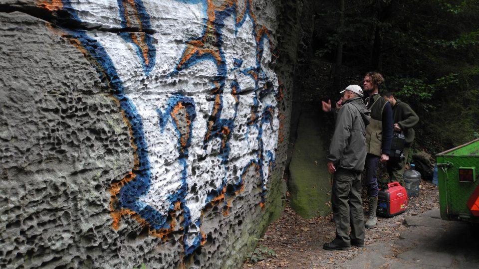 Neznámý vandal posprejoval pískovcovou skálu stříbrnou, modrou a červenou barvou