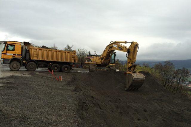 Dělníci odtěžují zeminu z horní části sesuvu nad rozestavěnou dálnicí