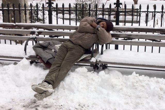 Bezdomovec v zimě na lavičce (ilustrační foto)