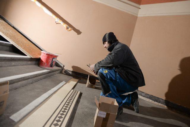 Řemeslníci na schodišti pracují na pokládání mozaikové dlažby