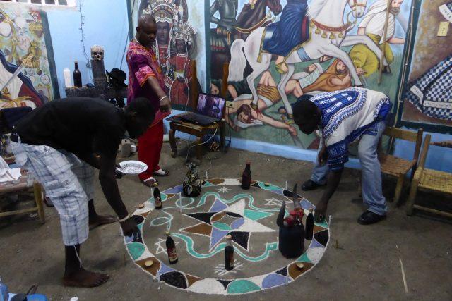 Vysypávání barevného vévé,  které jsou v kurzu v hlavním městě Haiti. Hlavní kněz přikazuje,  ostatní poslouchají | foto: Veronika Šulcová