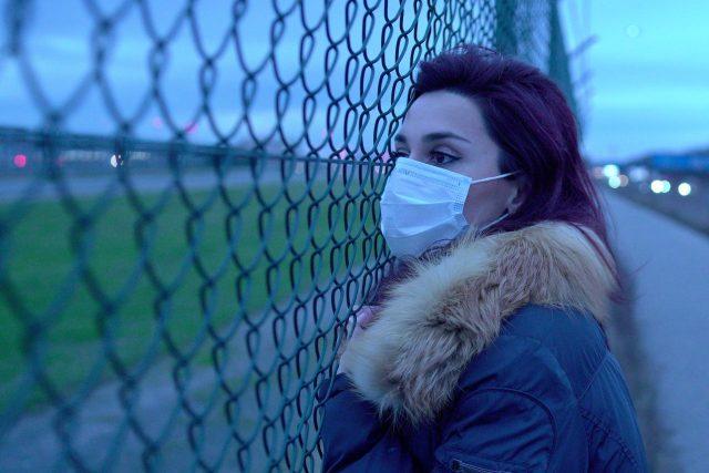 Mladá žena s rouškou u plotu | foto: Dimitri Karastelev,  Fotobanka Unsplash